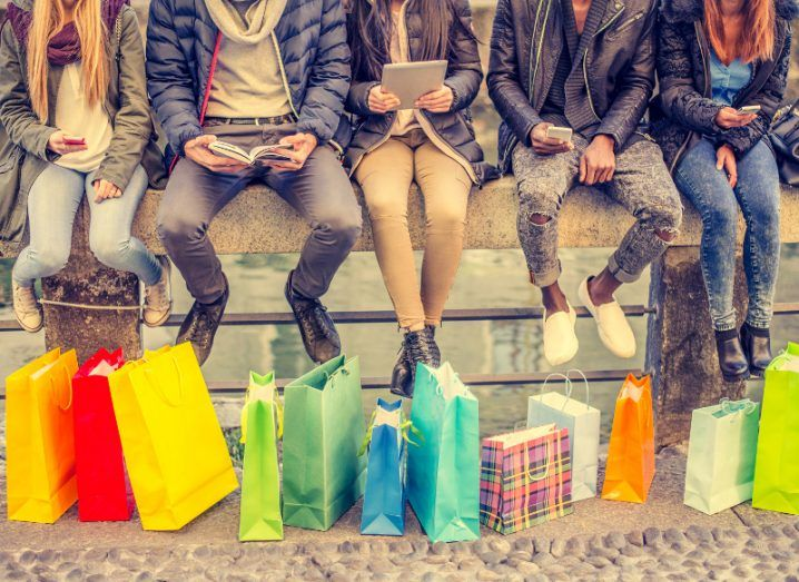 five people sitting at an outdoor fountain looking at phones and tablets with colourful shopping bags at their feet.