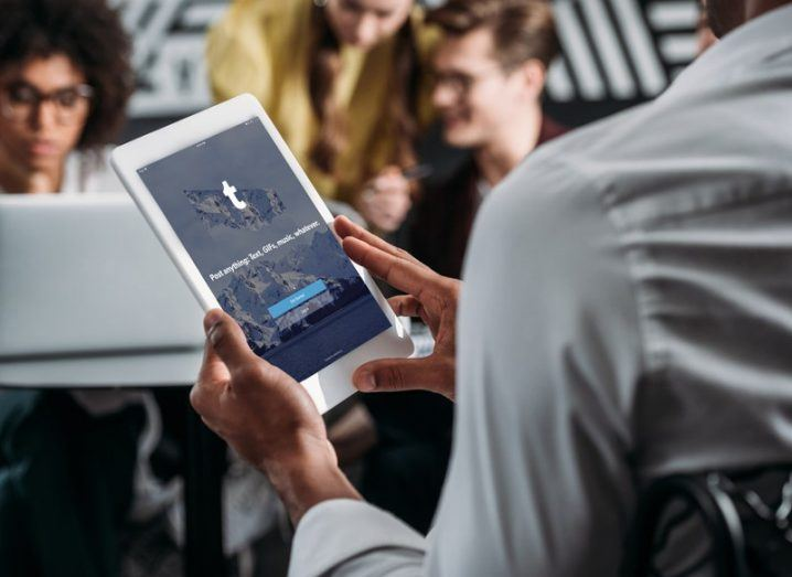 Picture of a man using Tumblr app on a tablet device in a crowded room.