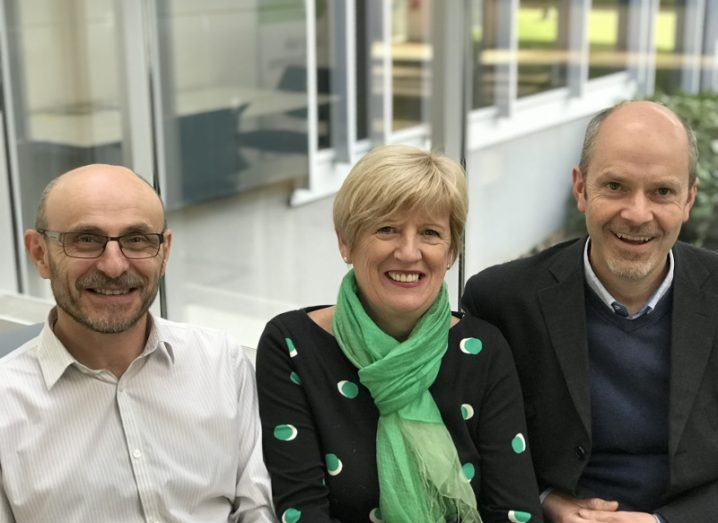 Two men sit either side of a blonde-haired woman in a green scarf.