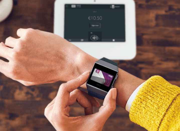 Person in yellow jumper makes a payment using a fitbit device with an AIB card on the screen.