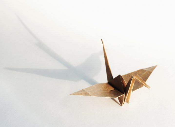 An origami crane made of brown paper casts a long shadow on a white surface.
