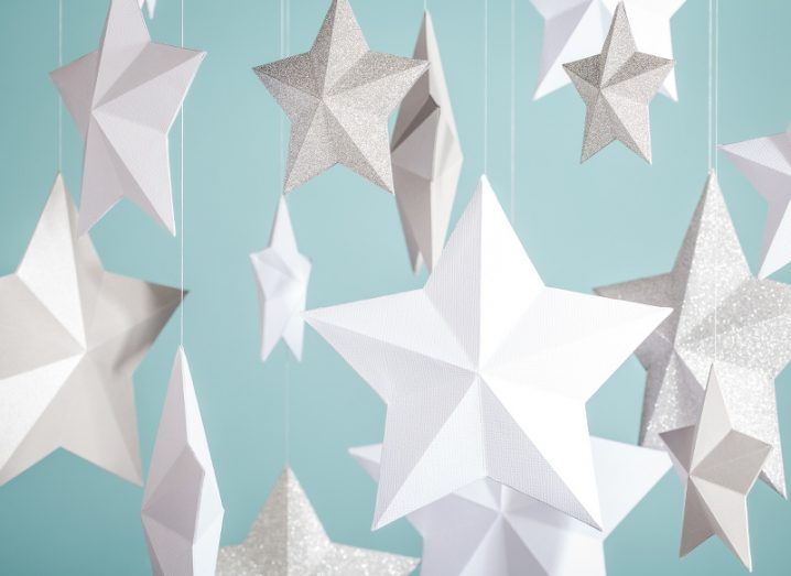 Hanging paper stars, some made from plain white card and others sparkling silver, against a light blue background.