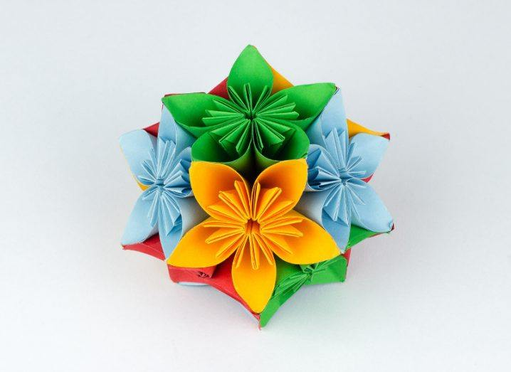 Origami flower in multiple colours on white background.