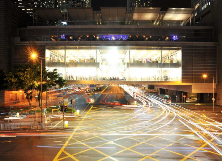 Apple Store above a busy intersection at night in Hong Kong.