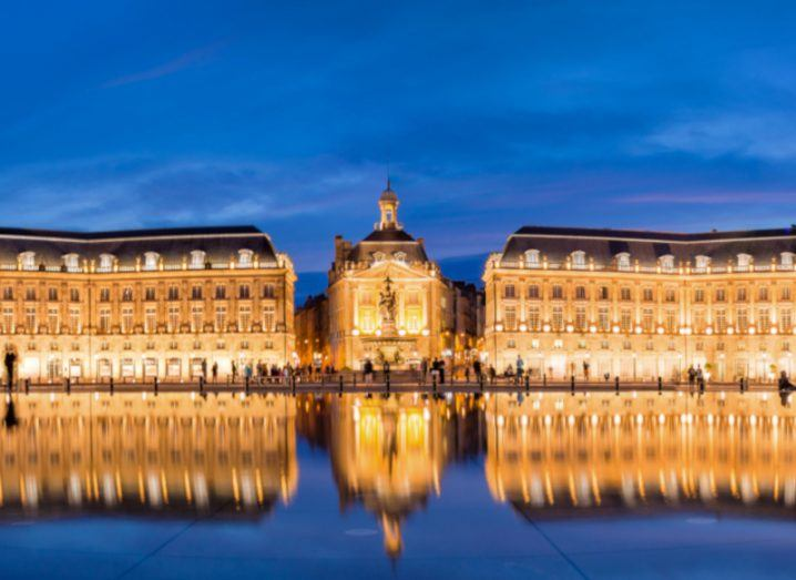 Place la Bourse in Bordeaux, mirrored in water by night.