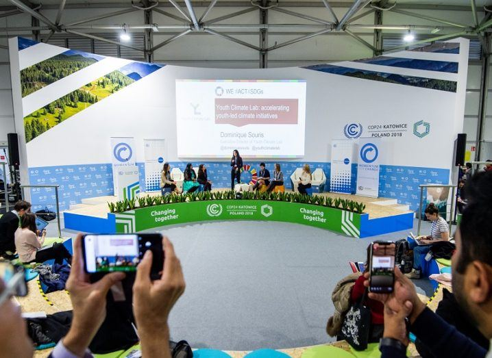 Journalists pointing cameras at a small stage with people speaking at COP24.