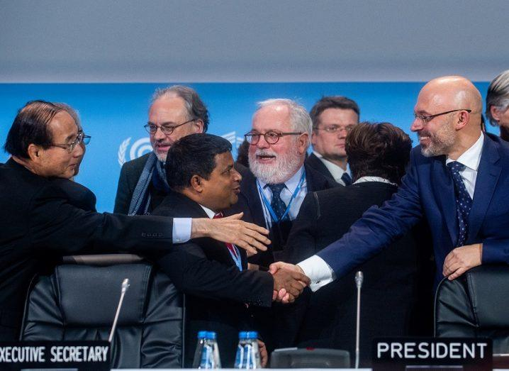 Members of the COP24 commitee shaking hands after the signing of agreement.
