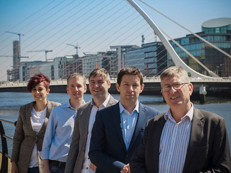 A woman and four men stand beside Liffey on a sunny day.