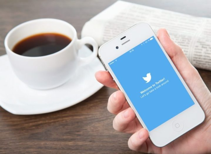 A hand holding a phone displaying the Twitter app, cup of black coffee in background.