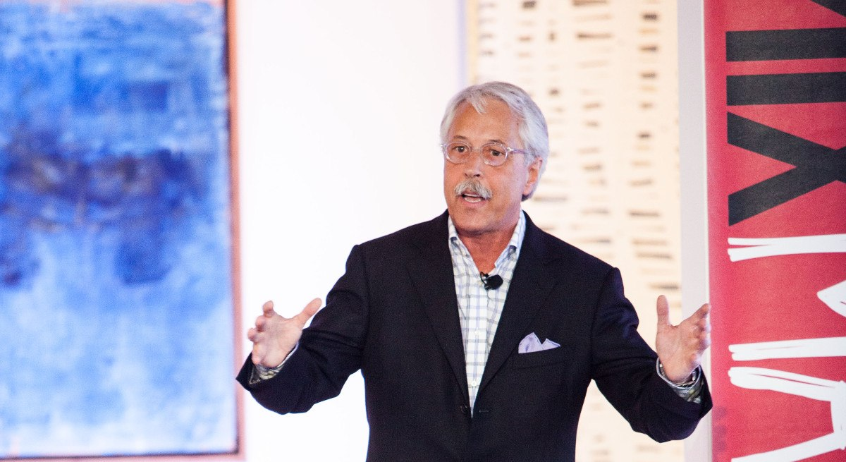 Gary Hamel is a man with white hair and a moustache. He's gesturing with his hands, speaking at a conference.