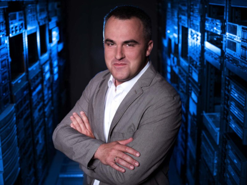 Man in grey jacket with arms folded standing in server room.