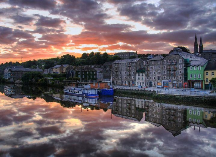 Beautiful harbour town of New Ross at dawn with clouds reflected on water.