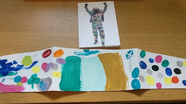 Strip of canvas on a table with a hand-painted Ireland flag and multi-coloured dots, with a spacesuit picture above.