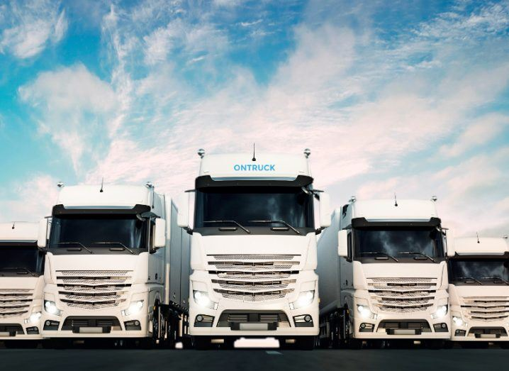 Line of white trucks under a blue cloudy sky.