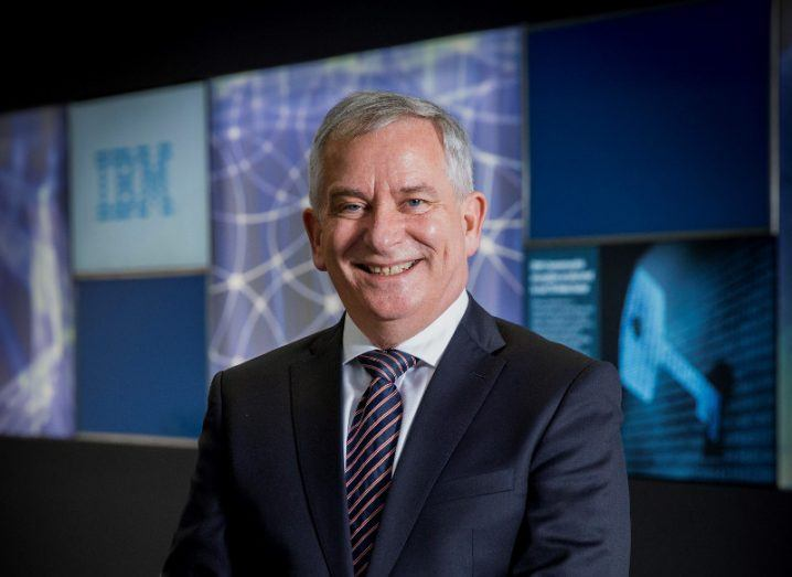 Man in navy suit and striped tie standing before screens with IBM emblazoned on them.