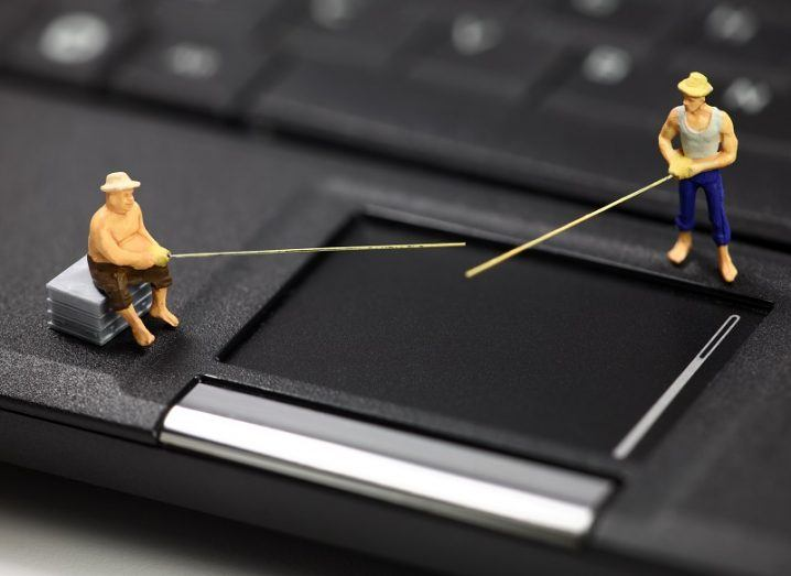 Miniature fisherman representing phishing scammers on a laptop.