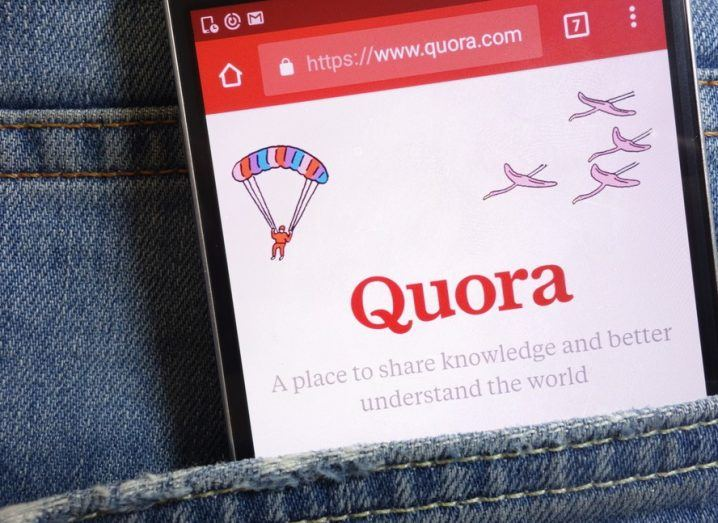 quora app on a smartphone in the pocket of a pair of blue jeans.