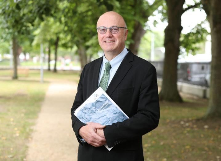 A man in a suit and glasses stands in a park holding the SFI 2017 Annual Report in his hands.