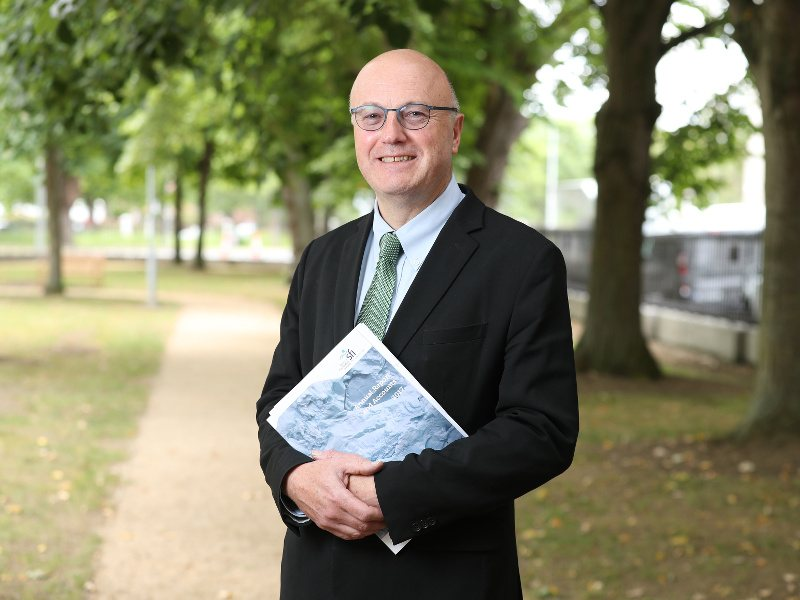 A bald man in a suit and glasses stands in a park holding the SFI 2017 Annual Report in his hands.