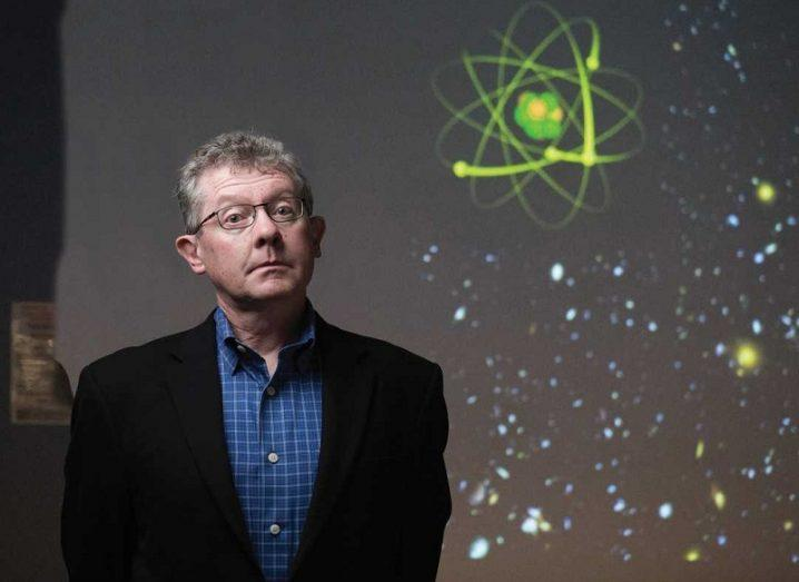 Seámus Davis looking quizzically in front of a projected image of an atom.