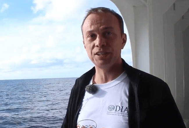 Sergei Lebedev standing beside the sea on a research vessel.
