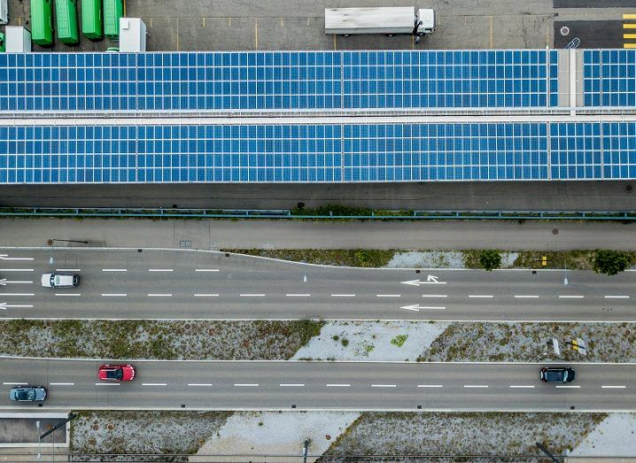 Bird's eye view of solar panels running parallel to two roadways with cars on them.