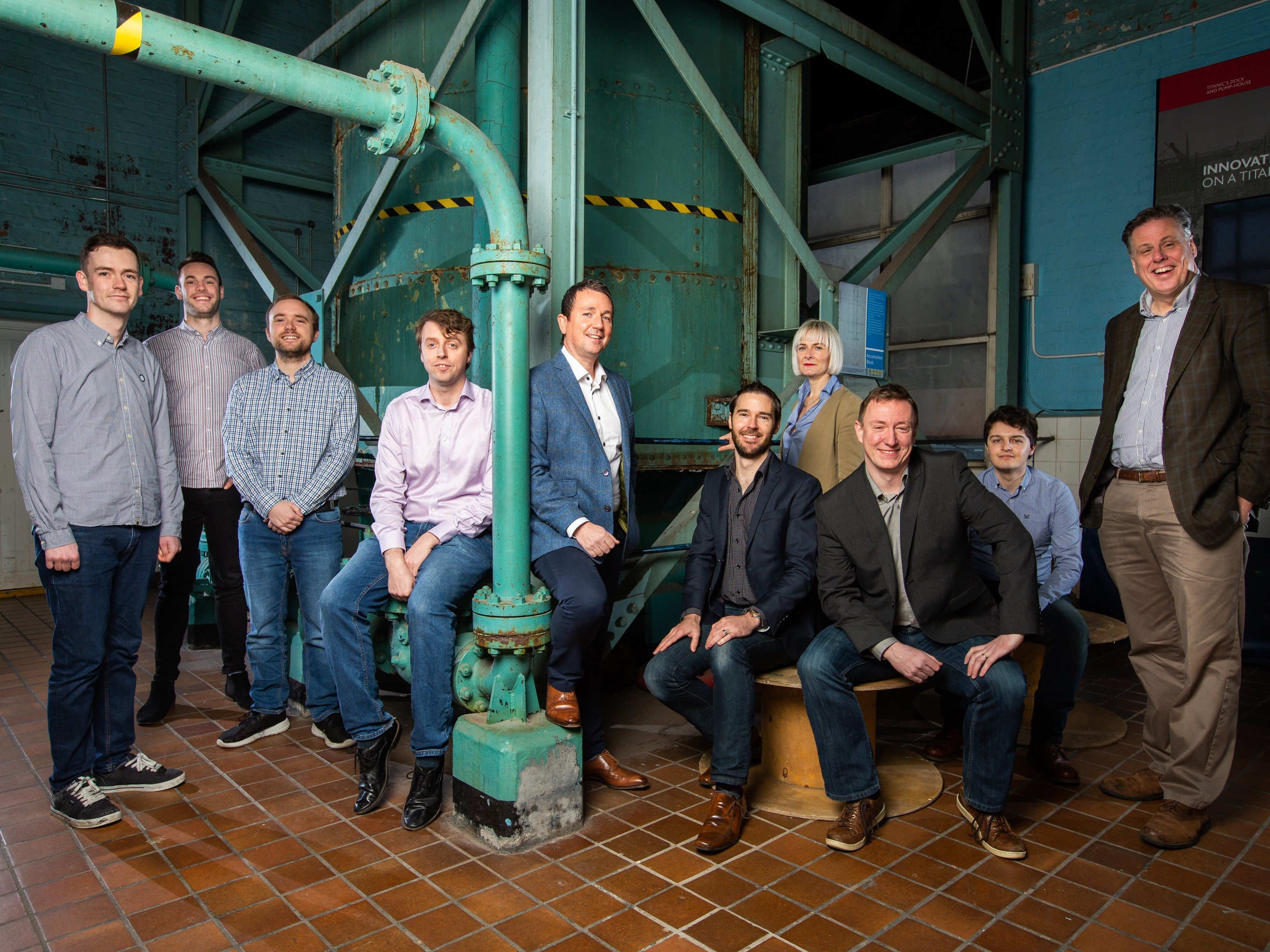 Ten people sitting and standing among green pipes.