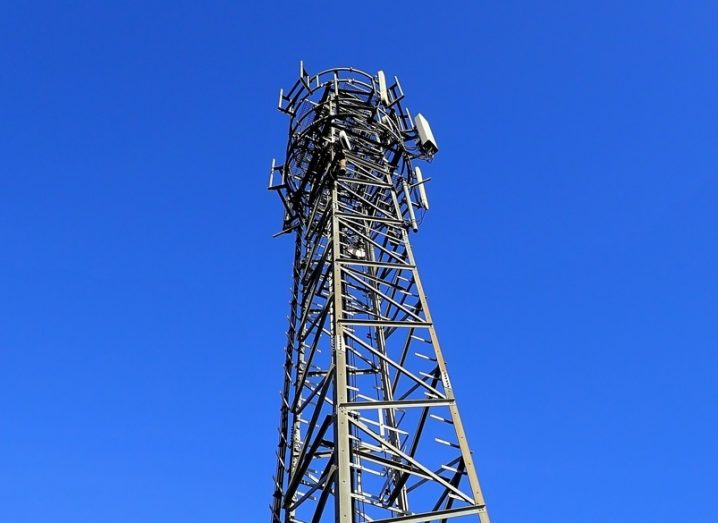 A mobile phone mast with a bright and cloudless blue sky in the background.