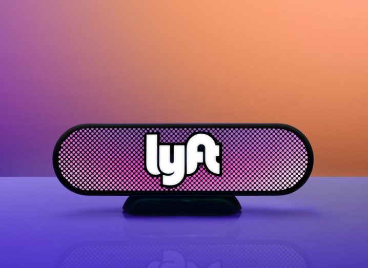 Lyft car light with logo fixed to the front on an orange and purple background.