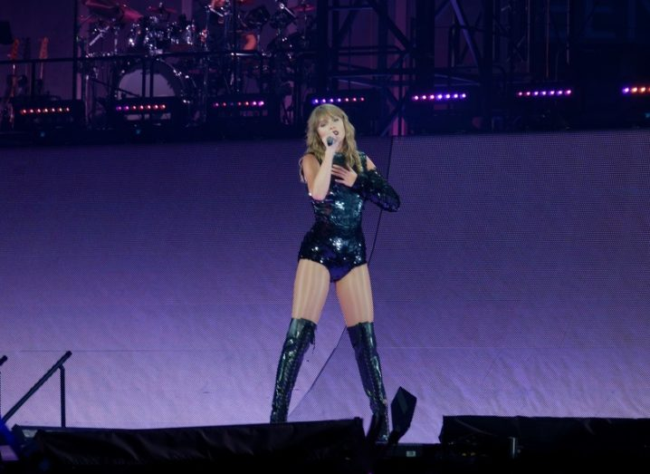 Taylor Swift performing on stage in a black bodysuit and boots with a purple backdrop behind her.