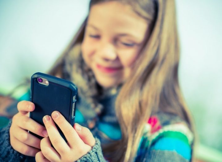 A young girl playing with a mobile device and smiling.