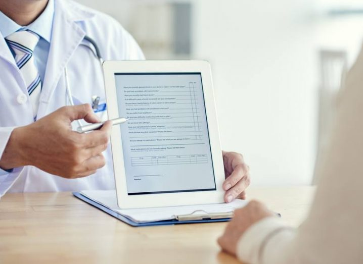 Doctor showing survey on tablet computer to the patient.