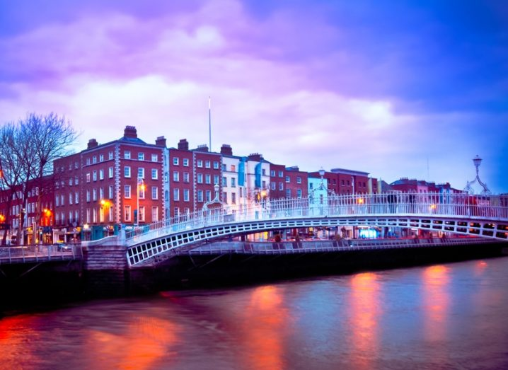 The Ha'penny Bridge over the River Liffey in Dublin at sunset with purple skies.