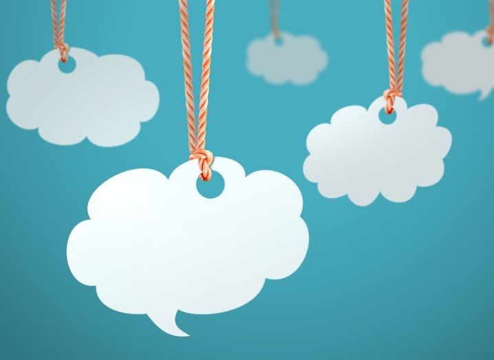 Cloud shaped paper cutouts hanging on string with a blue wall in the background.