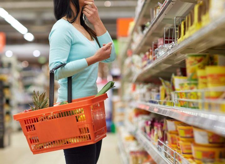 Woman in a blue jumper holding an orange basket and deciding between items on a supermarket shelf.