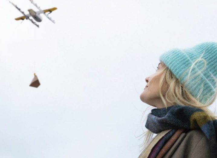 A blonde woman in a blue wooden hat looking upwards at a Wing drone in the sky.