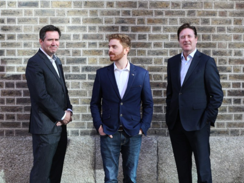 Three men in suits standing against a wall.