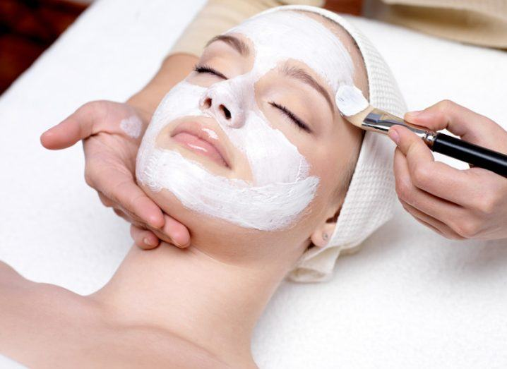 woman receiving facial mask at beauty salon.