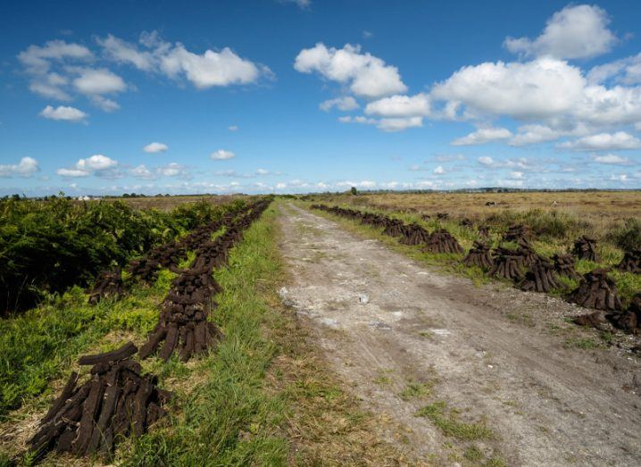 A bog road in Ireland lined by sods of turf leading off under a blue cloudy sky.