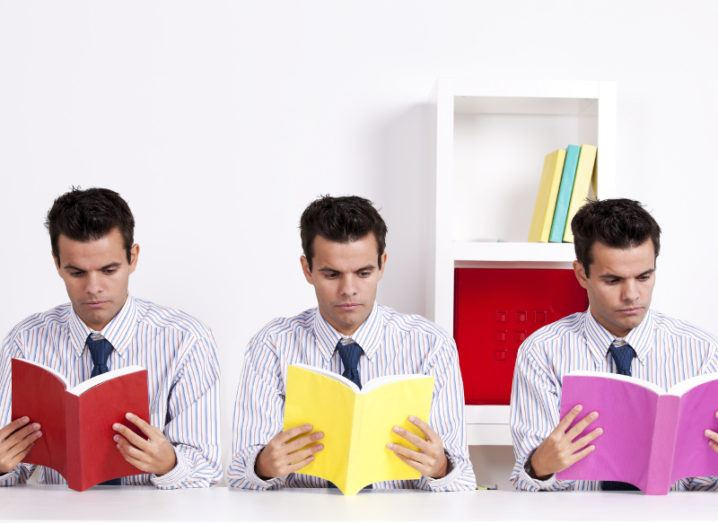 three identical businessmen with dark hair and striped shirts reading a red, yellow and pink book.