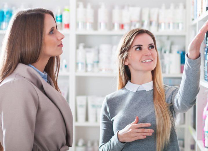 blonde woman in grey jumper gesturing to shelf in pharmacy beside brunette woman customer in beige coat.
