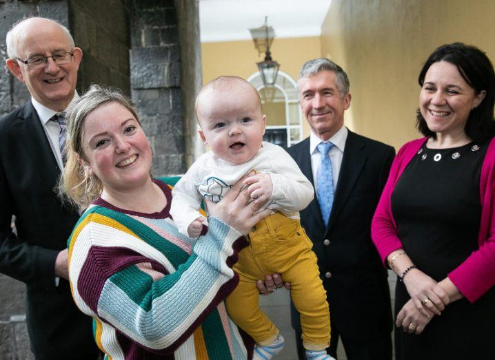 woman holding up her smilingbaby son beside two male and one female health representatives.