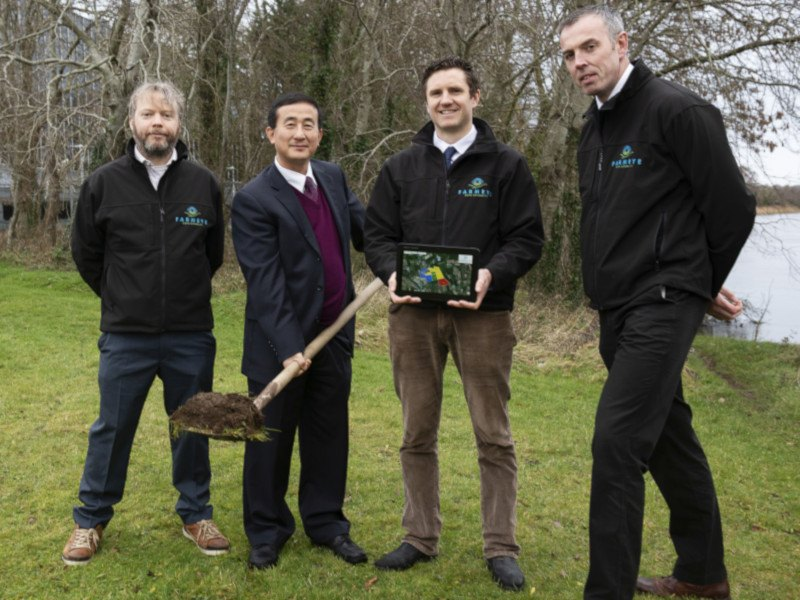 Four men in a field, one with a shovel of soil.