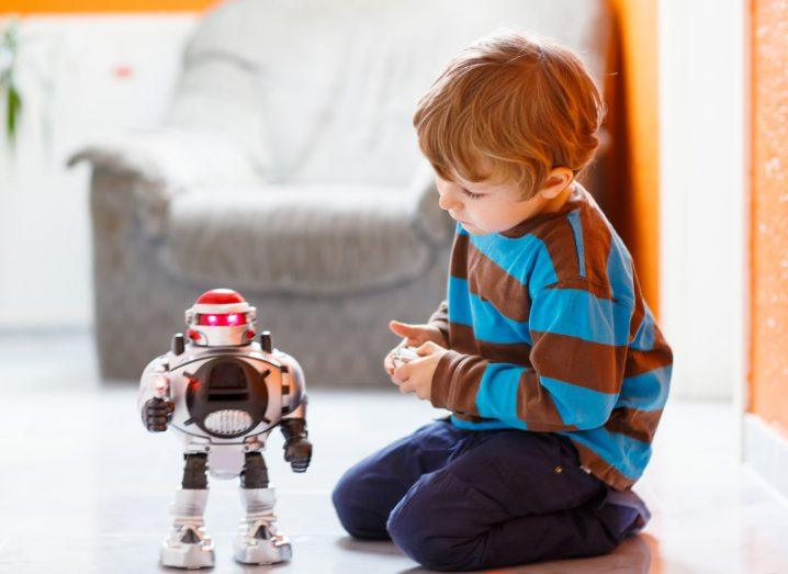 Little blond boy in striped top playing with smart robot toy at home indoors.