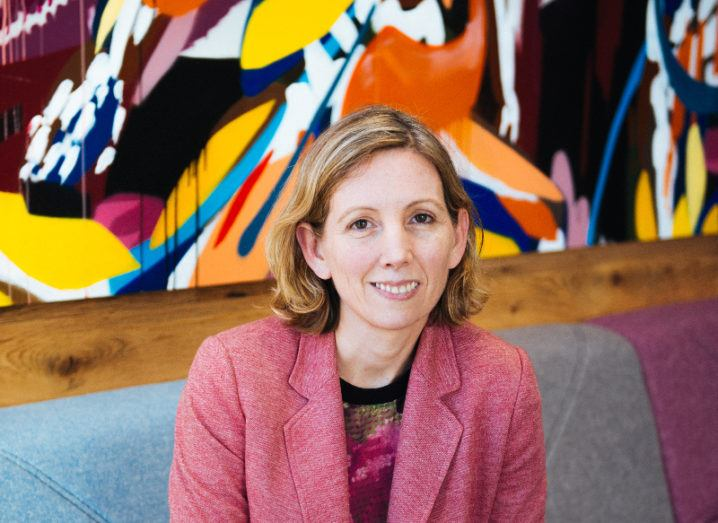 A woman in a pink a blazer and colourful top smiles on a cushioned bench below a striking and colourful abstract painting.