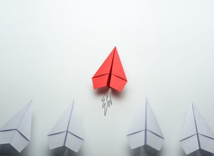 A row of white paper aeroplanes with one red one taking off.