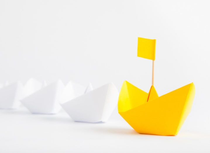 A row of white paper origami boats being led in front by a yellow boat with a yellow flag.