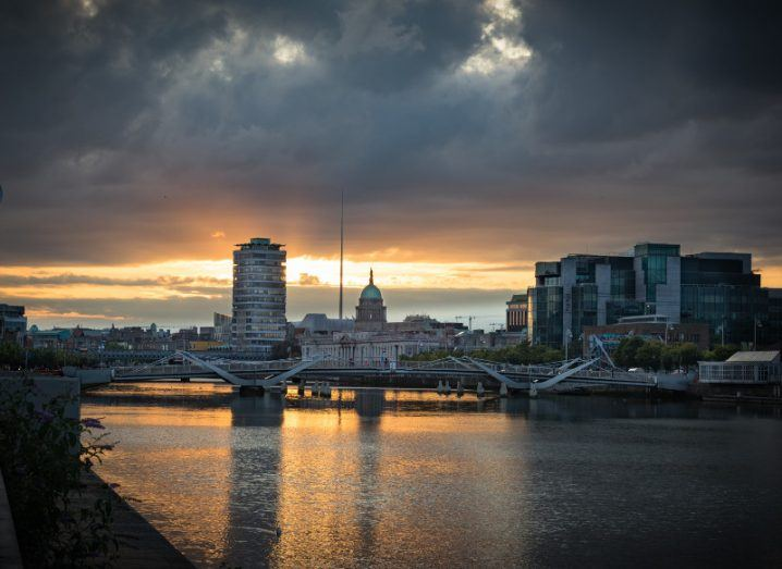 Storm clouds gather over Dublin city centre with dying sun reflected on Liffey.