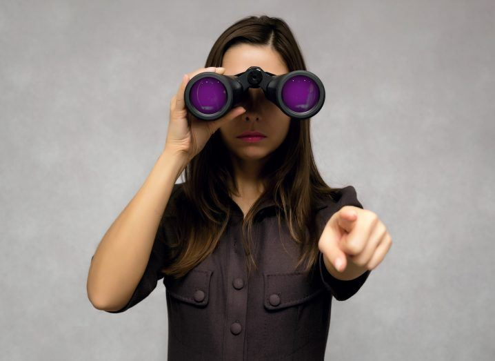 Young woman looking through binoculars with purple lenses and pointing with her index finger.