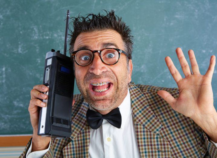 Man in checkered jacket holds retro walkie-talkie.